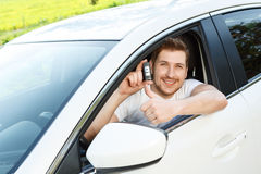 Man thumbing up in car with alarm system Royalty Free Stock Image