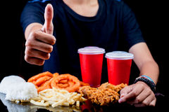 Man thumbs up in front of junk fast food package stock image