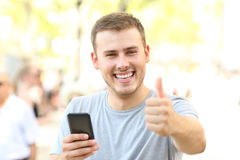 Man with thumbs up holding phone looking at you Royalty Free Stock Photos