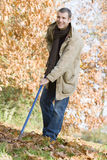 Man tidying autumn leaves Stock Images
