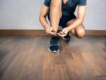 Man tie shoelaces on floor. Man tie shoelaces on wooden floor Stock Photos