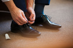 Man ties his shiney new black leather business shoes. Stock Photo
