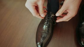 Man ties the laces on black shoes stock video footage