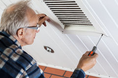 Man tightening the bolts on ventilation grille. Horizontal Stock Photography