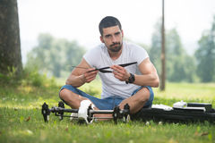 Man Tightening Drone Propeller in Nature stock photo