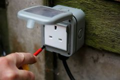 Man tightening external socket box with an electrical screwdriver Stock Images