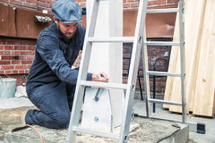 Man tightens mettalical nuts with a wrench. A strong construction man in dark construction overalls and a gray cap tightens mettalical nuts with a wrench on a Royalty Free Stock Photography