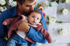 The man tightly hugs his child and kisses him gently in the head. Fatherly tenderness. The girl is studying the room. The men tightly hugs his child and kisses stock photos