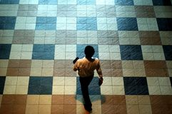 Man on Tile Floor. A man walking ahead with confident on tiles floor Royalty Free Stock Photos