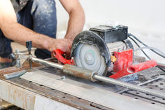 Man tiler construction worker electric porcelain cuts tiles Tile Royalty Free Stock Image