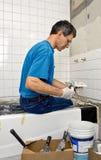 Man Tiling A Bathroom Wall. Man applying ceramic tile to a bathtub enclosure wall Royalty Free Stock Photography