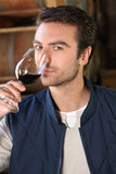 Man tilting glass of wine. Man tasting and smelling red wine Stock Image
