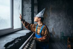 Man in tinfoil cap looking out the window, UFO Royalty Free Stock Images