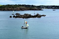 Man in a tiny wooden sailboat in Port Manech Brittany France Europe stock images