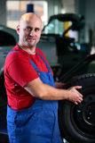 A man with tire. A car mechanic hold tire for change closeup shot stock image
