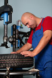 Man with a tire. A mechanic working on a tire, changing wheel in a garage with a professional tool royalty free stock photography