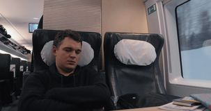 Sleeping man in express train. Man is tired and falling asleep during the travel by first class in express train stock footage