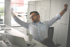 Man tired stretching in office. Business man in office. Royalty Free Stock Image