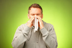 Man with tissue. Man having a cold holding tissue and blowing his nose Stock Photos