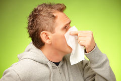 Man with tissue. Man having a cold holding tissue and blowing his nose Stock Images