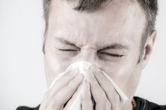 Man with tissue is sneezing Stock Images