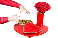 Man About to Grab Valentines Chocolates. A table is set up with a red vase with red roses beside an open heart shaped box of chocolates.  A mans hands are shown Royalty Free Stock Images