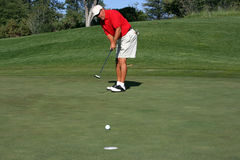 Man about to make putt. Man concentrating on making putt on green, focus on golfer Royalty Free Stock Photos