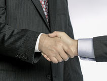 Man to man Handshake in Suit and Tie; up close viewpoint of businessmen. Close up of two male/man's shaking hands.  Both men in dark suit; one man in red tie Royalty Free Stock Photo