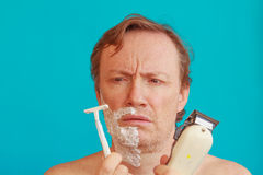 A man to shave must choose between the razor and the razor-blade. A man with shaving -foam about to shave but is undecided whether to choose razor or razor-blade Royalty Free Stock Images