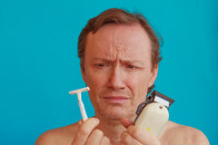 A man to shave must choose between the razor and the razor-blade Royalty Free Stock Photos
