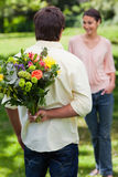 Man about to surprise his friend with a bouquet of flowers Royalty Free Stock Photo