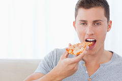 A man about to take a bite out of his pizza Royalty Free Stock Photography
