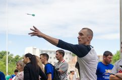 Man to throw dart at target in amateur competitions. Komsomolsk-on-Amur, Russia - August 8, 2016. Public open Railroader`s day. man to throw dart at target in royalty free stock photos