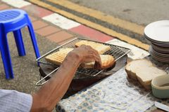 Man toasting bread on an open coal fire. At a market on the side of the road, Chiang Mai, Northern Thailand Stock Image