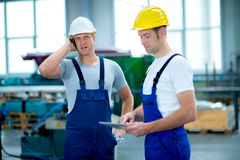 Man together in factory with tablet PC and cellphone Stock Photo