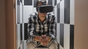 Man in the toilet in headphones getting experience in using VR-headset. Close-up shot of a man in headphones getting experience in using VR-headset stock footage