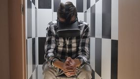Man in the toilet in headphones getting experience in using VR-headset. Close-up shot of a man in headphones getting experience in using VR-headset stock video footage