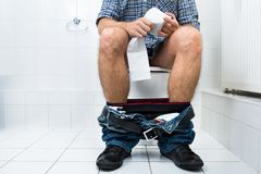 Man in toilet holding tissue paper roll Stock Photography