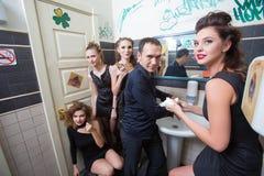 Man in toilet met dronken vrouwen stock foto