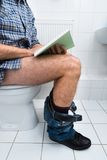Man in toilet reading book Royalty Free Stock Photo