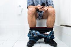Man in toilet using cellphone Stock Photos