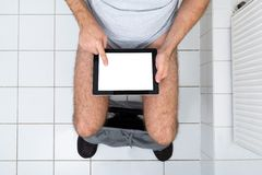 Man in toilet using digital tablet Stock Photography