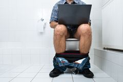 Man in toilet using laptop. Close-up Of A Man Sitting On Commode Using Laptop stock images