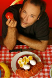 Man with tomato. Man holding a tomato while sitting at a table Stock Photo