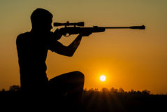 Man took aim with your sniper rifle. Young man took aim with your sniper rifle at sunset Royalty Free Stock Photography