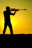 Man took aim with your sniper rifle. Young man took aim with your sniper rifle at sunset Royalty Free Stock Photos