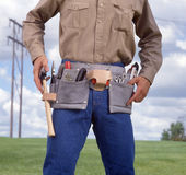 Man with tool belt. Blue sky and electrical pole in the background stock photo