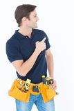 Man with tool belt around waist pointing against white background Royalty Free Stock Photography