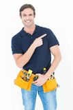 Man with tool belt around waist pointing over white background Stock Photography
