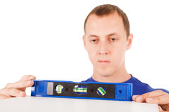 Man with tool level isolated in white background. Royalty Free Stock Images
